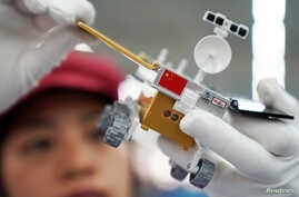 A worker inspects a scale model of the moon rover for China's Chang'e 4 lunar probe, at a factory in Dongguan, Guangdong province, China, Nov. 16, 2018.
