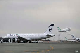 FILE - An Iranian Mahan Air passenger plane takes off as a plane of Iran's national air carrier, Iran Air, is parked at left, at Mehrabad airport in Tehran, Feb. 7, 2016.