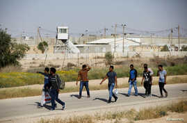 African migrants walk on a road after being released from Saharonim Prison in the Negev desert, Israel, April 15, 2018.