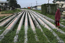 FILE - A girl walks on a gas pipeline running through Okrika community near Nigeria's oil hub city of Port Harcourt.