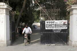 A man rides on a motorbike past a poster installed at the entrance gate of the Pakistan Medical Association (PMA) office in Karachi, Pakistan, April 8, 2015.