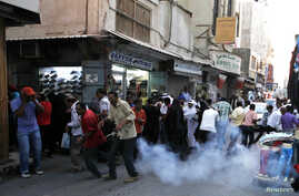 Protesters and shoppers run for cover from a sound grenade thrown by riot police to disperse protesters, during an anti-government protest in the capital Manama, October 26, 2012.