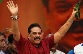 """Sri Lanka's former president Mahinda Rajapaksa waves at his supporters as he arrives at a protest rally to launch a plan to topple the current government, accusing it of failing in its """"management and development of the country"""" in Colombo, Sri Lanka"""