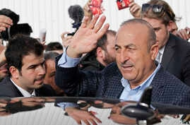 FILE - Turkish Foreign Minister Mevlut Cavusoglu, waves to supporters as he is reflected on a car after a campaign gathering in Metz, eastern France, March 12, 2017.