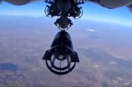 In this photo made from the footage taken from Russian Defense Ministry official web site on Monday, Oct. 5, 2015 a bomb is released from Russian Su-24M jet fighter in Syria.
