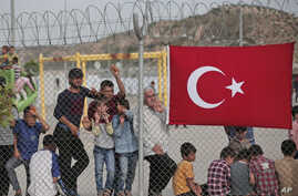 Migrants stand behind a fence at the Nizip refugee camp in Gaziantep province, southeastern Turkey, April 23, 2016.