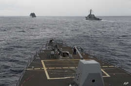 FILE - U.S. Navy ships are seen from the bridge of the guided-missile destroyer USS Spruance, in the South China Sea, Oct. 17, 2016, in a photo provided by the U.S. Navy.