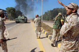 Soldiers from a force aligned with Libya's new unity government walk along a road during an advance on the eastern and southern outskirts of the Islamic State stronghold of Sirte, in this still image taken from video on June 9, 2016.