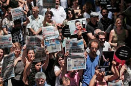 FILE - Protesters demonstrate against the jailing of two journalists and an academic, outside the offices of Ozgur Gundem, a pro-Kurdish publication, in Istanbul, June 21, 2016.