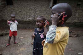 Olematu, 3 (left), and Ibrahim, 4, talk on toy phones in a village near Kenema, Sierra Leone. Their 15-year-old sister, Betty, has taken charge after their mother's death from Ebola. Betty survived an Ebola infection. (© UNICEF / Bindra)