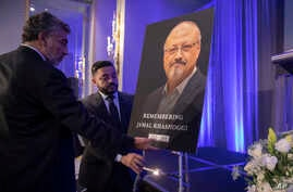FILE - Mongi Dhaouadi, left, and Ahmed Bedier set up an image of slain Saudi journalist Jamal Khashoggi before an event to remember Khashoggi, a columnist for The Washington Post who was killed inside the Saudi Consulate in Istanbul.