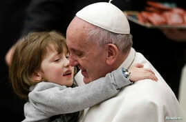 Pope Francis holds a child as he leads the weekly audience in Paul VI's hall at the Vatican, Jan. 20, 2016.