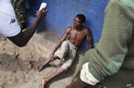 Jean Claude Niyonzima, a suspected member of the ruling party's Imbonerakure youth militia, sits under soldiers' protection from a mob of demonstrators after he came out of hiding in a sewer in the Cibitoke district of Bujumbura, Burundi, May 7, 2015...