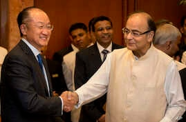 Indian Finance Minister Arun Jaitley, right, shakes hand with World Bank President Jim Yong Kim, in New Delhi, India on June 30, 2016.