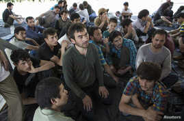 FILE - Suspected Uighurs from China's troubled far-western region of Xinjiang, sit inside a temporary shelter after they were detained at the immigration regional headquarters near the Thailand-Malaysia border in Hat Yai, Songkla, March 14, 2014.