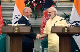 Indian Prime Minister Narendra Modi, right, shakes hands with Afghan President Ashraf Ghani after signing of bilateral agreements in New Delhi, India, Wednesday, Sept. 14, 2016.