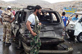 This citizen journalism image provided by Edlib News Network shows Syrian rebels with damaged cars at the scene where a car bomb exploded at a crossing point near Syria's border with Turkey, Sept. 17, 2013.