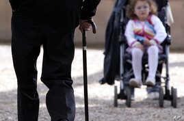 FILE - An elderly man (L) uses a cane to support his walk as he approches a child being pushed in a stroller, in Rome, Italy, April 27, 2007. Globally, life expectancy worldwide rose by five years between 2000 and 2015.