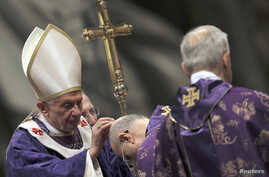 Pope Benedict XVI sprinkles ashes on Cardinal Tarcisio Bertone (C) during the Ash Wednesday mass at the Vatican February 13, 2013. Thousands of people are expected to gather in the Vatican for Pope Benedict's Ash Wednesday mass, which is expected to