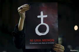A woman holds up a poster with female symbol during a demonstration outside the Congress demanding policies to prevent femicides in Buenos Aires, Argentina, June 3, 2015.