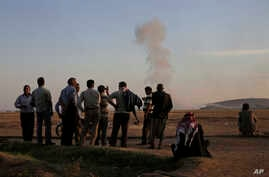 Turkish Kurds watch as airstrikes hit Kobani, inside Syria, as fighting intensifies between Syrian Kurds and the militants of Islamic State group, in Mursitpinar, on the outskirts of Suruc, at the Turkey-Syria border, Wednesday, Oct. 8, 2014.