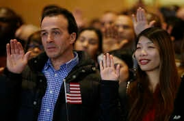 Weizhen Cai from China, right, and Ahmed Haloui from Morocco recite the oath of citizenship during a celebration of the naturalization off approximately 200 new citizens of the United State , Nov. 30, 2017 at the John F. Kennedy Library in Boston.