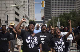 Activists raise their hands as they demand justice for the killing of Michael Brown while marching to the Thomas F. Eagleton United States Courthouse from City Hall in downtown St. Louis, Missouri, August 26, 2014.