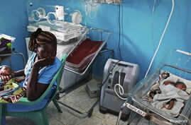 FILE - A woman holds her newborn baby in a nursery, while a newborn nearby is attached to a ventilator at Juba Teaching Hospital in Juba April 3, 2013. South Sudan has one of the highest maternal mortality rates in the world.