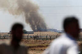 In this photo taken from the Turkish side of the border between Turkey and Syria, in Akcakale, southeastern Turkey, people watch as smoke from a US-led airstrike rises over the outskirts of Tal Abyad, Syria, June 15, 2015.
