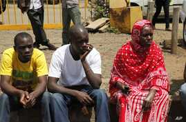 Relatives wait for the bodies of slain police officers to arrive at Wilson Airport Nairobi, Kenya, Tuesday, Nov. 13, 2012. Suspected cattle thieves hid on a high hill and ambushed and killed at least 34 police officers pursuing them over the weekend