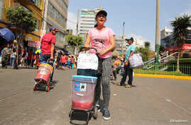 FILE - Days Laguado, a migrant from Venezuela, sells a traditional Venezuelan drink known as 'Tizana' at Gamarra textile cluster in Lima's district of la Victoria, Peru, May 11, 2017.