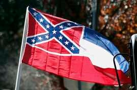 FILE - The state flag of Mississippi is unfurled by Sons of Confederate Veterans and other groups on the grounds of the state Capitol in Jackson, Mississippi, Jan. 19, 2016. An effort to erase the Confederate battle emblem from the Mississippi flag