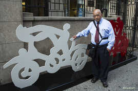 Mexican artist Gilberto Aceves Navarro poses for a portrait with two of his bicycle sculptures in New York City, June 30, 2014.