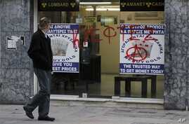 "Man passes entrance of a store that buys gold vandalized with Greek word ""thievess,"" Nicosia, Cyprus, March 25, 2013."