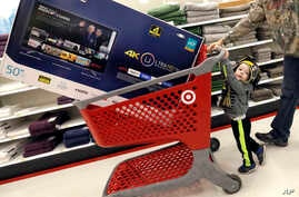 FILE - Hunter Harvey and his dad, C.J., plan to purchase a big screen TV at Target, in Wilmington, Massachusetts, Nov. 25, 2016. The U.S. Commerce Department reported Tuesday, Nov. 29, 2016, that the economy grew faster than expected between July and