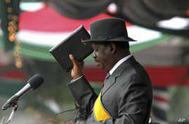 Kenya's Prime Minister Raila Odinga reads the oath of office during the promulgation of the New Constitution at Uhuru Park in Nairobi, Aug 27, 2010