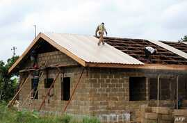 Workers roof building at the new Bakassi Town, which is being developed to relocate displaced citizens, Cross River State, Bakassi Peninsula, Aug. 2008 file photo.