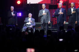 Former Presidents from right, Barack Obama, Bill Clinton, George W. Bush, George H.W. Bush and Jimmy Carter place their hands on their heart for the national anthem at the opening of a hurricanes relief concert in College Station, Texas, Oct. 21, 201