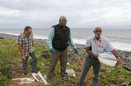 A Malaysian expert, center, looks for debris from the ill-fated Malaysia Airlines flight MH370 on a beach in Saint-Andre de la Reunion, on Reunion Island, in the Indian Ocean, Aug. 4, 2015.