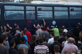 Protesters rock a riot police bus in the town of Mytilene on the northeastern Aegean island of Lesbos, May 3, 2018.
