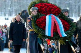 Russian President Vladimir Putin, left, takes part at a wreath laying ceremony at the Piskaryovskoye Cemetery, in St. Petersburg, Jan. 27, 2019, where most of the Leningrad Siege victims were buried during World War II.