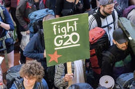 A passenger of the special protest train 'ZuG20' carries a poster 'fight G20' while arriving at the central station in Hamburg, Germany, July 6, 2017.