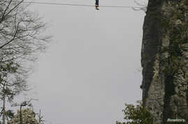 FILE - American climber Dean Potter walks barefoot on a rope which is connected between two mountain peaks in Enshi, Hubei province, April 22, 2012.