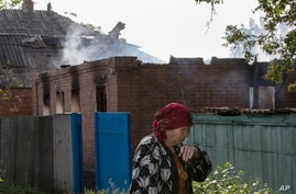 An elderly local woman passes a house destroyed by shelling in Semyonovka, a town near Slovyansk, Ukraine, on May 23, 2014.