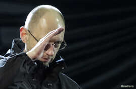 Ukraine opposition leader Arseniy Yatsenyuk, named to the post of interim prime minister, gestures on the stage during a rally in Independence Square in Kyiv, Feb. 26, 2014.