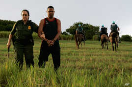 FILE - An unidentified Dominican migrant is escorted by a Border Patrol officer after being detained by Puerto Rico police near La Esperanza beach in the northern coastal town of Manati, Puerto Rico, Oct. 8, 2007.