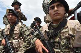Peruvian military and police get ready during the 'Mercury' joint operation against illegal mining, Feb. 19, 2019, in the Amazon jungle over the river basin of the Madre de Dios region, in southeast Peru.