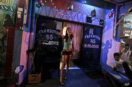 In this Thursday, June 19, 2014 photo, a 'karaoke girl' shouts protests against the city government's move to close down Dolly prostitution complex upon seeing reporters walking past her karaoke parlor at the red-light district in Surabaya, Indonesia