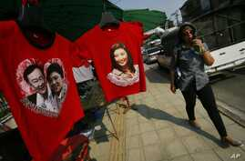 A pro-government supporter passes t-shirts with portraits of Prime Minister Yingluck Shinawatra and her self-exiled brother Thaksin at the gate of the National Anti-Corruption Commission office in Bangkok, Thailand, Thursday, Feb. 27, 2014. Thailand'