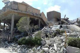 FILE - In this photo released by the Syrian official news agency SANA, shows the damage of the Syrian Scientific Research Center which was attacked by U.S., British and French military strikes to punish President Bashar Assad for suspected chemical a
